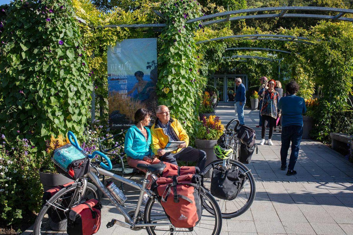 Entlang der Seine à vélo: Paar, das in der Sonne in Giverny sitzt