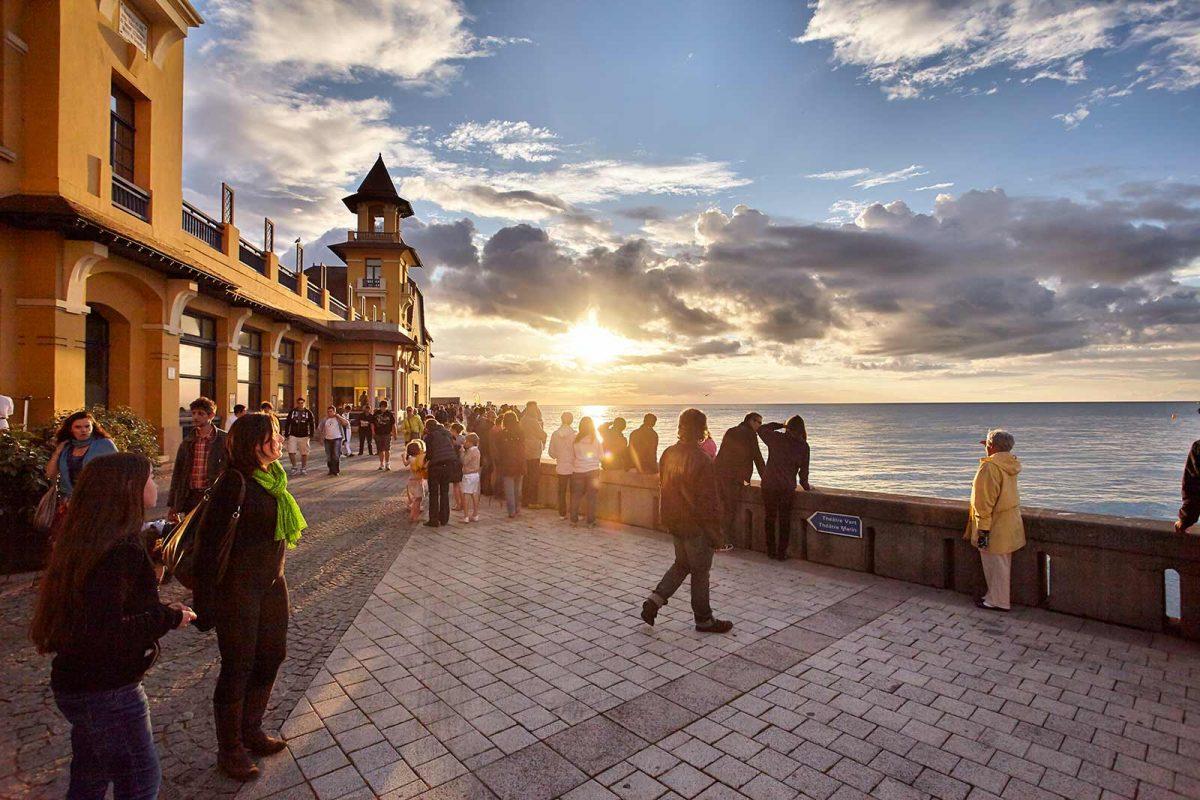 Promeneurs au coucher de soleil devant le casino de Granville