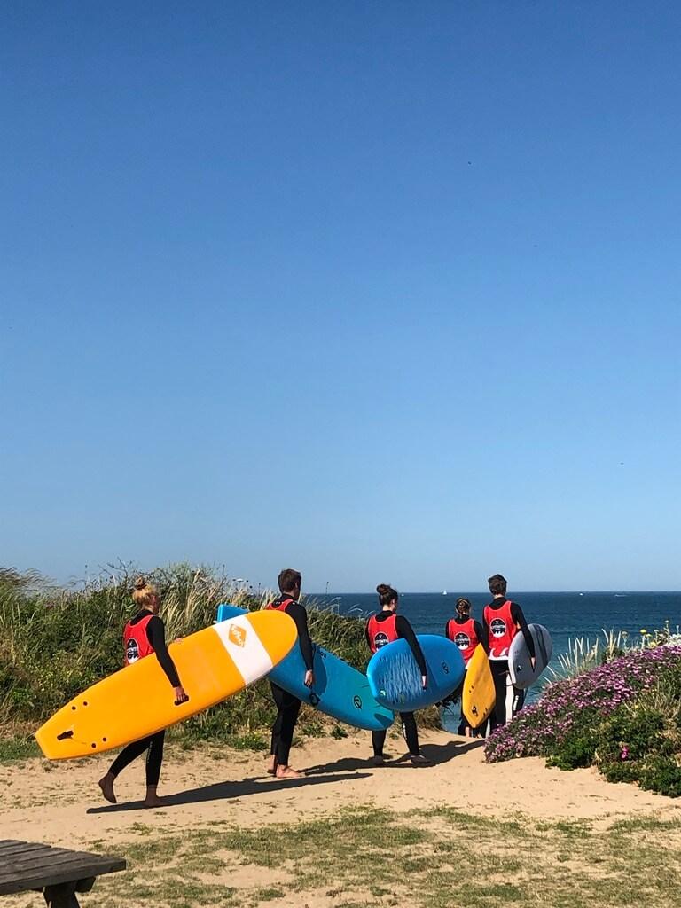 Gruppe Surferinnen und Surfer auf dem Weg zum Meer