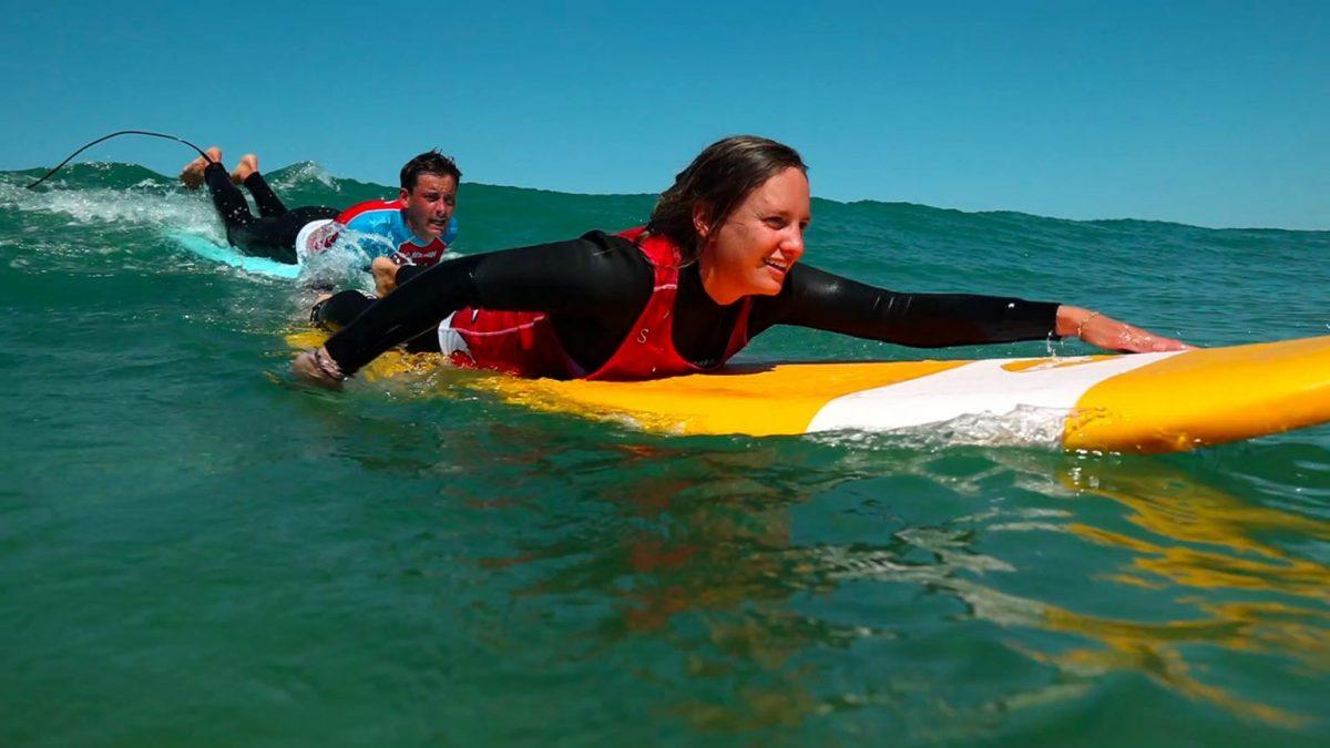 Frau paddelt auf dem Surfbrett zur nächsten Welle