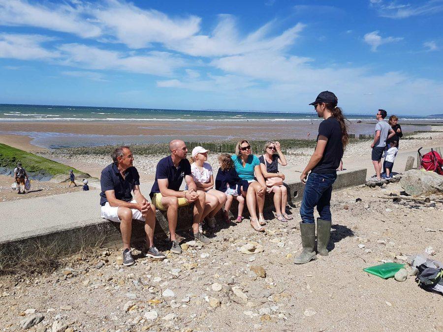 Gruppe hört Guide Jonas am Strand von Villers-sur-Mer zu.