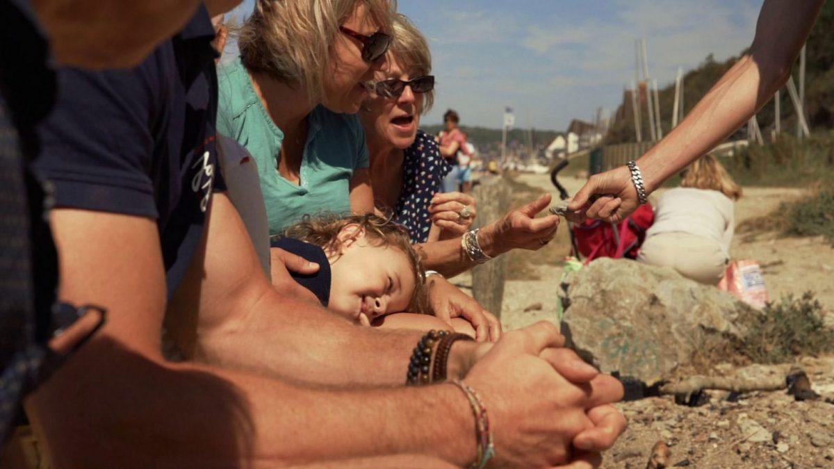 Frau inspiziert Fossil in Villers-sur-Mer